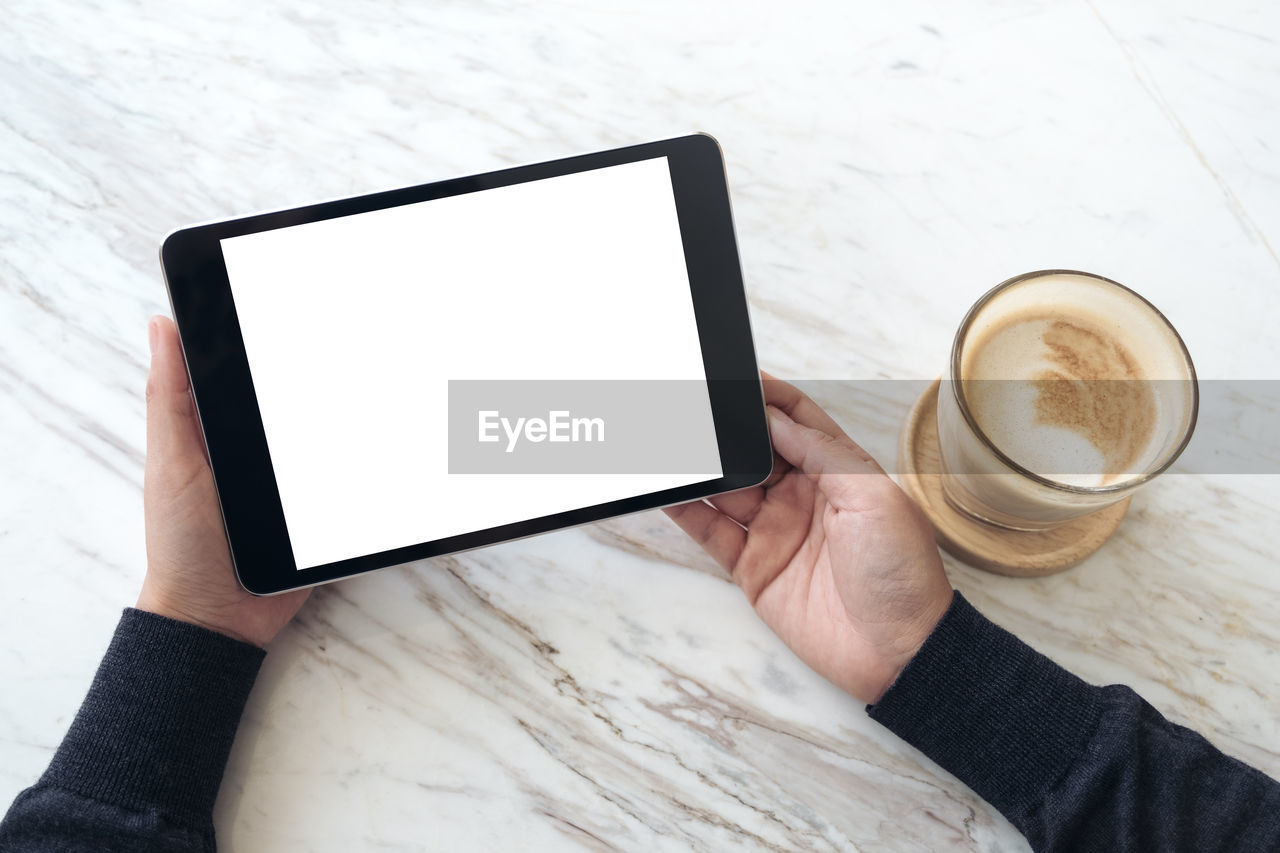 coffee, coffee - drink, wireless technology, drink, cup, technology, coffee cup, mug, human hand, holding, communication, screen, refreshment, connection, food and drink, hand, table, portable information device, touch screen, one person, hot drink, frothy drink, blank