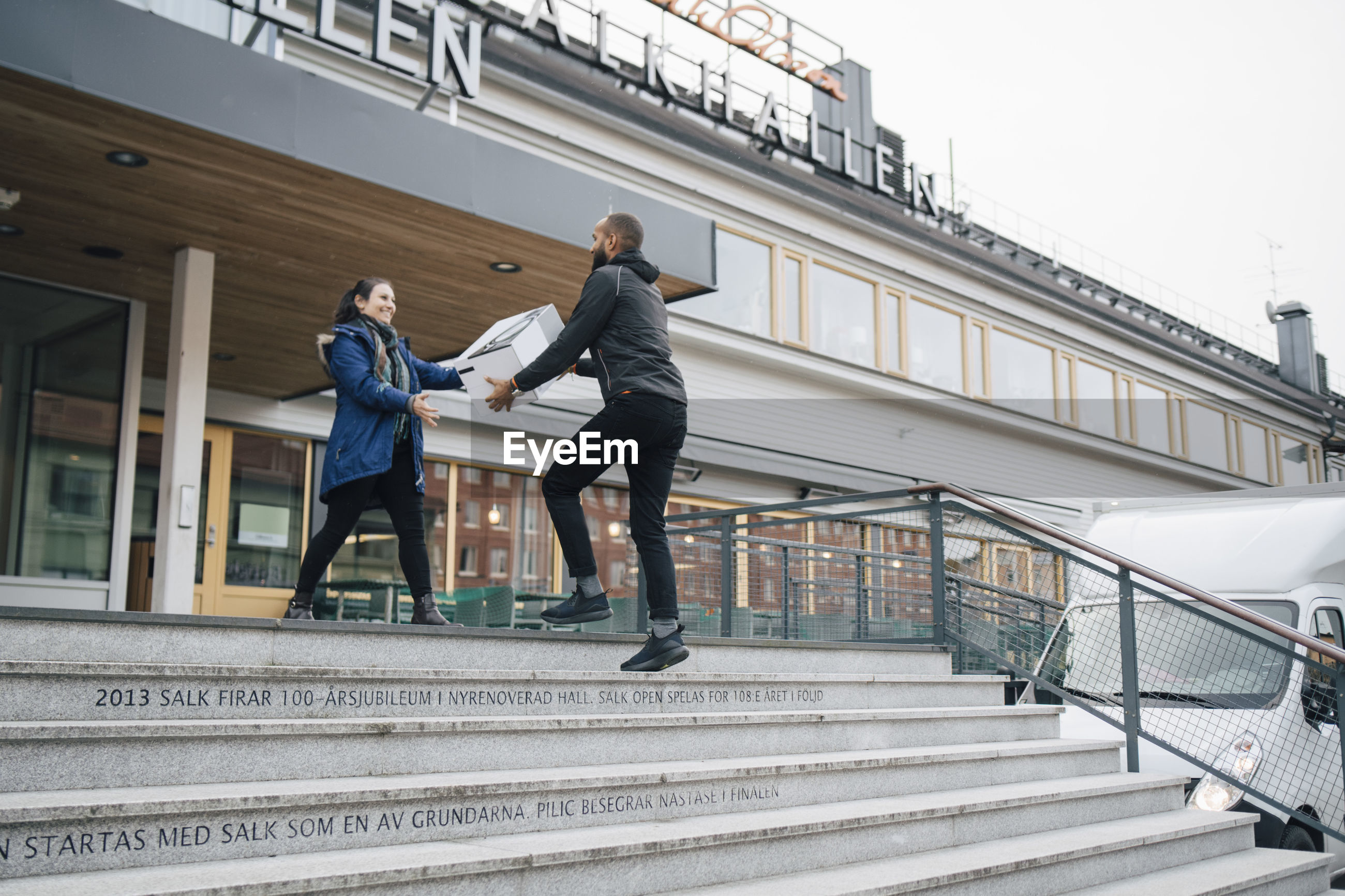 LOW ANGLE VIEW OF PEOPLE WALKING ON STAIRCASE AGAINST BUILDING