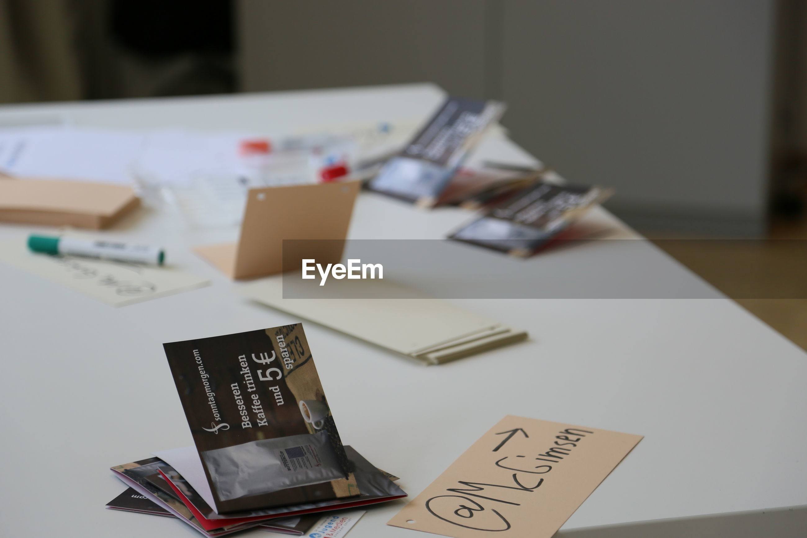 indoors, text, communication, western script, book, table, still life, paper, education, close-up, selective focus, no people, high angle view, document, pen, focus on foreground, desk, home interior, page, number