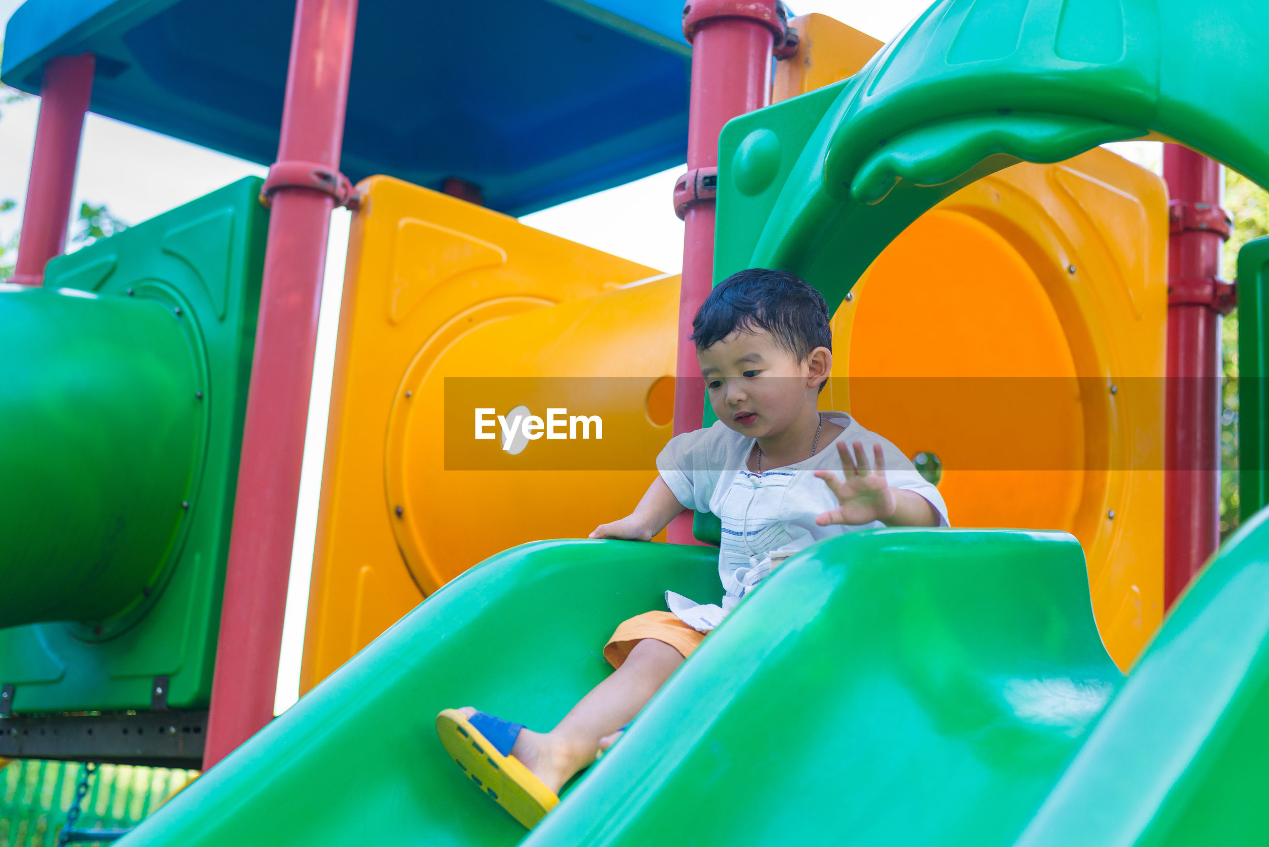 Full length of cute boy sitting on slide at playground