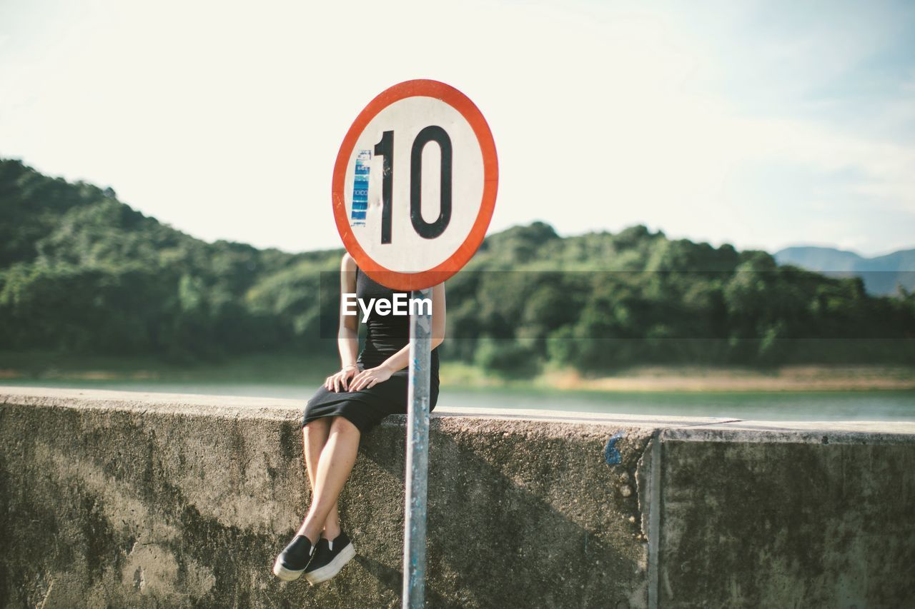 Woman sitting on retaining wall behind speed limit signboard