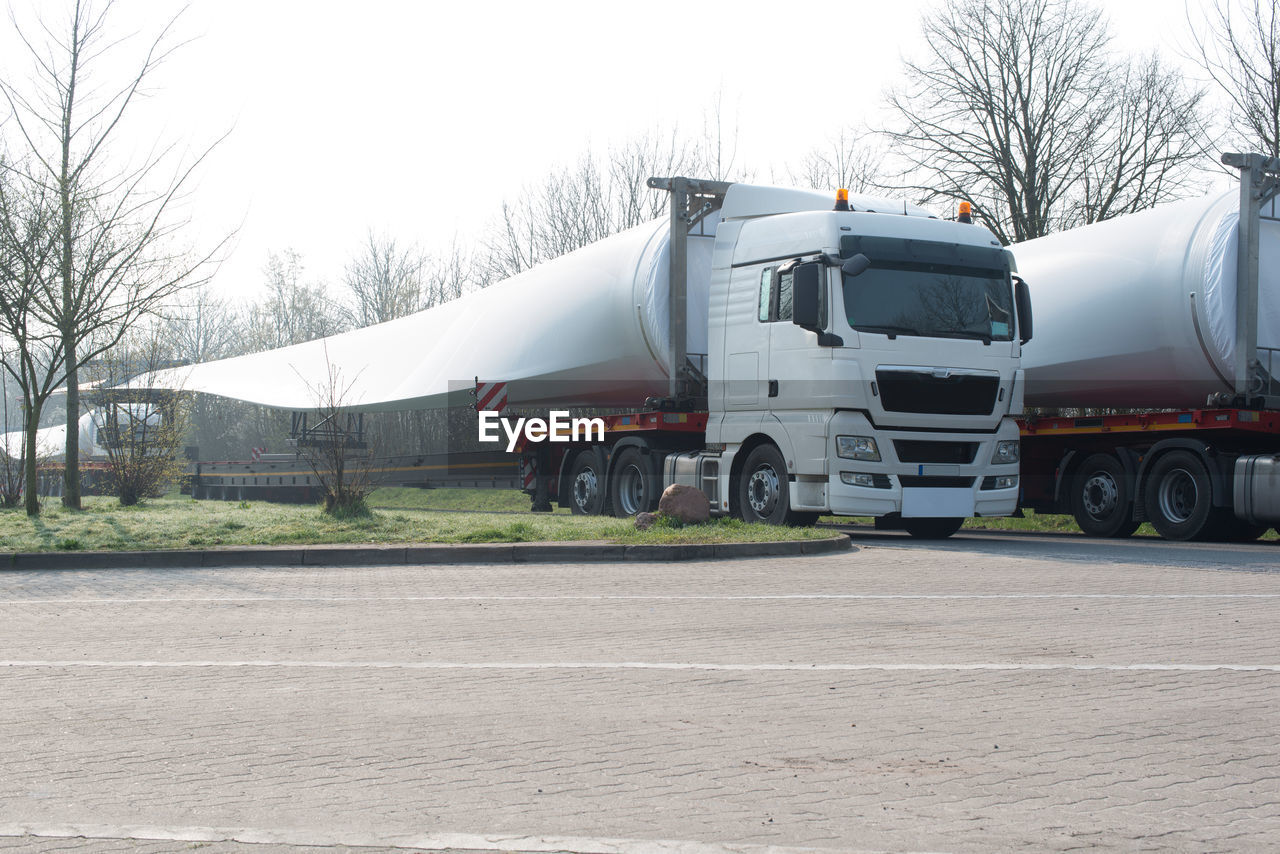 Close-up of windmill blade over trucks on road