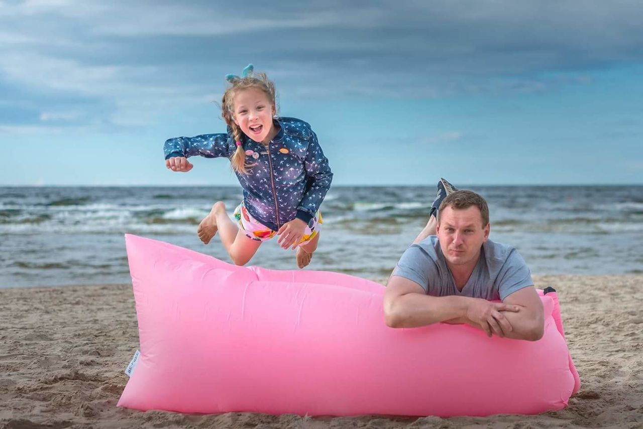 Portrait of father and daughter with pool raft at beach against cloudy sky
