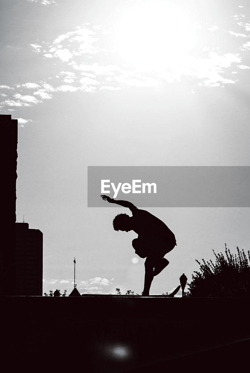 Silhouette man skateboarding against sky
