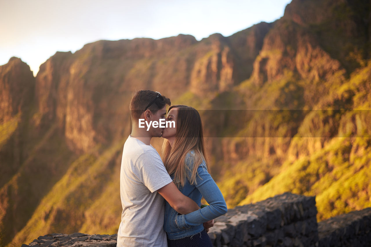 Side view of couple kissing against mountains