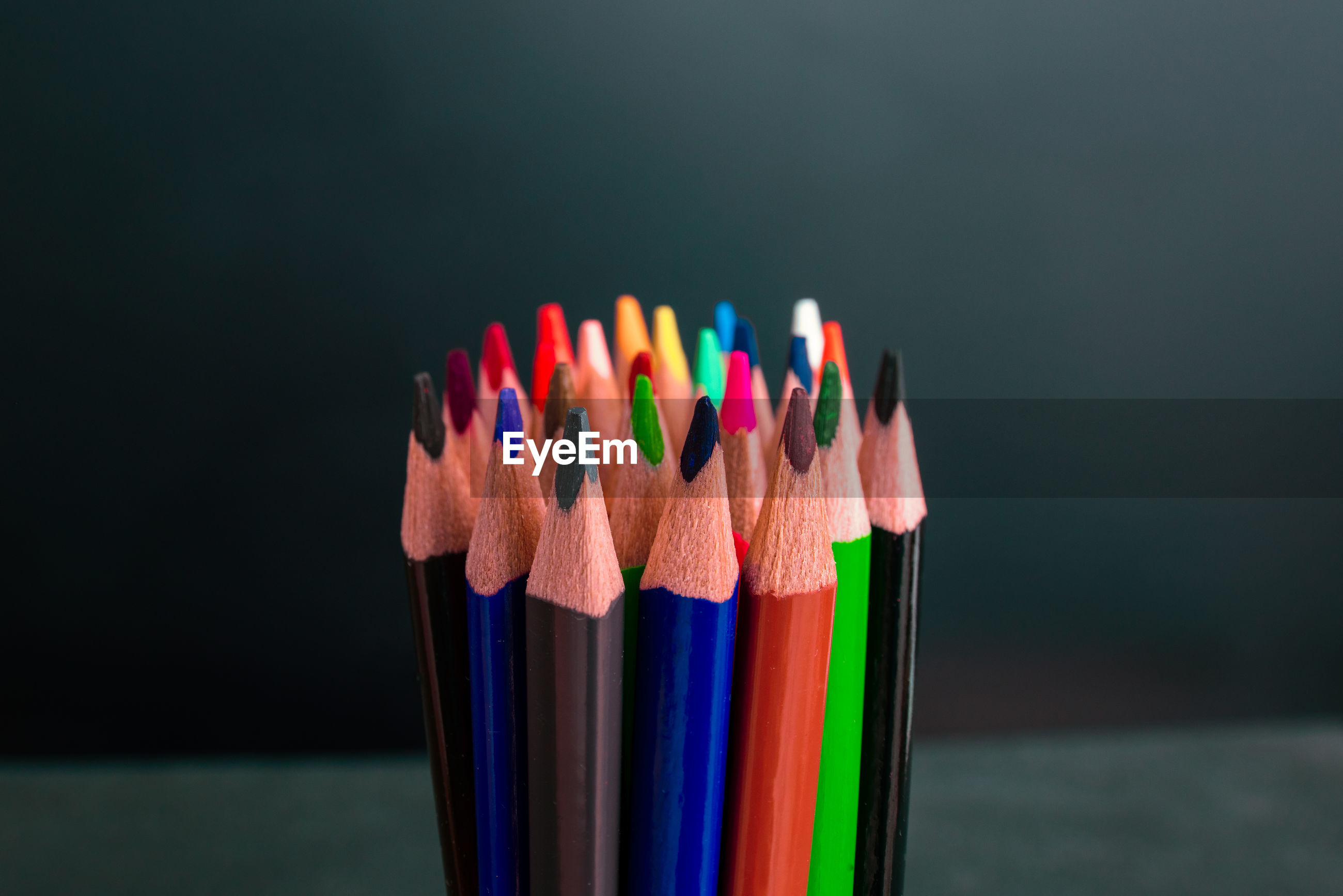 Close-up of multi colored pencils on table against black background