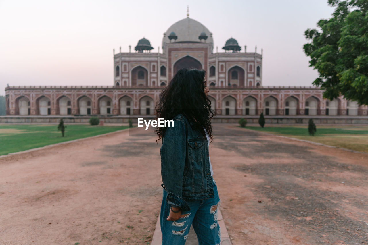 REAR VIEW OF WOMAN STANDING AT HISTORIC BUILDING