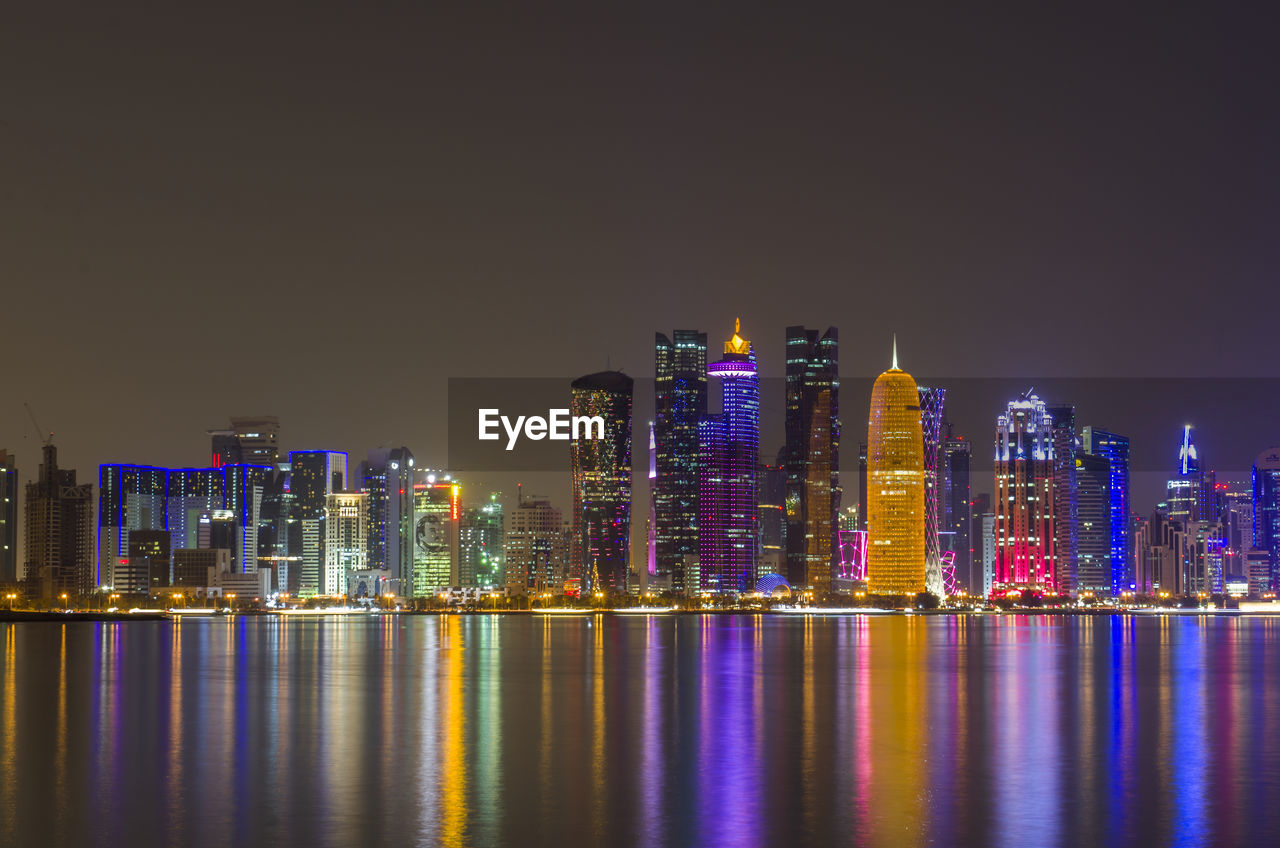 building exterior, architecture, built structure, night, building, city, water, illuminated, waterfront, office building exterior, sky, reflection, urban skyline, cityscape, landscape, skyscraper, modern, tall - high, no people, outdoors, financial district, nightlife
