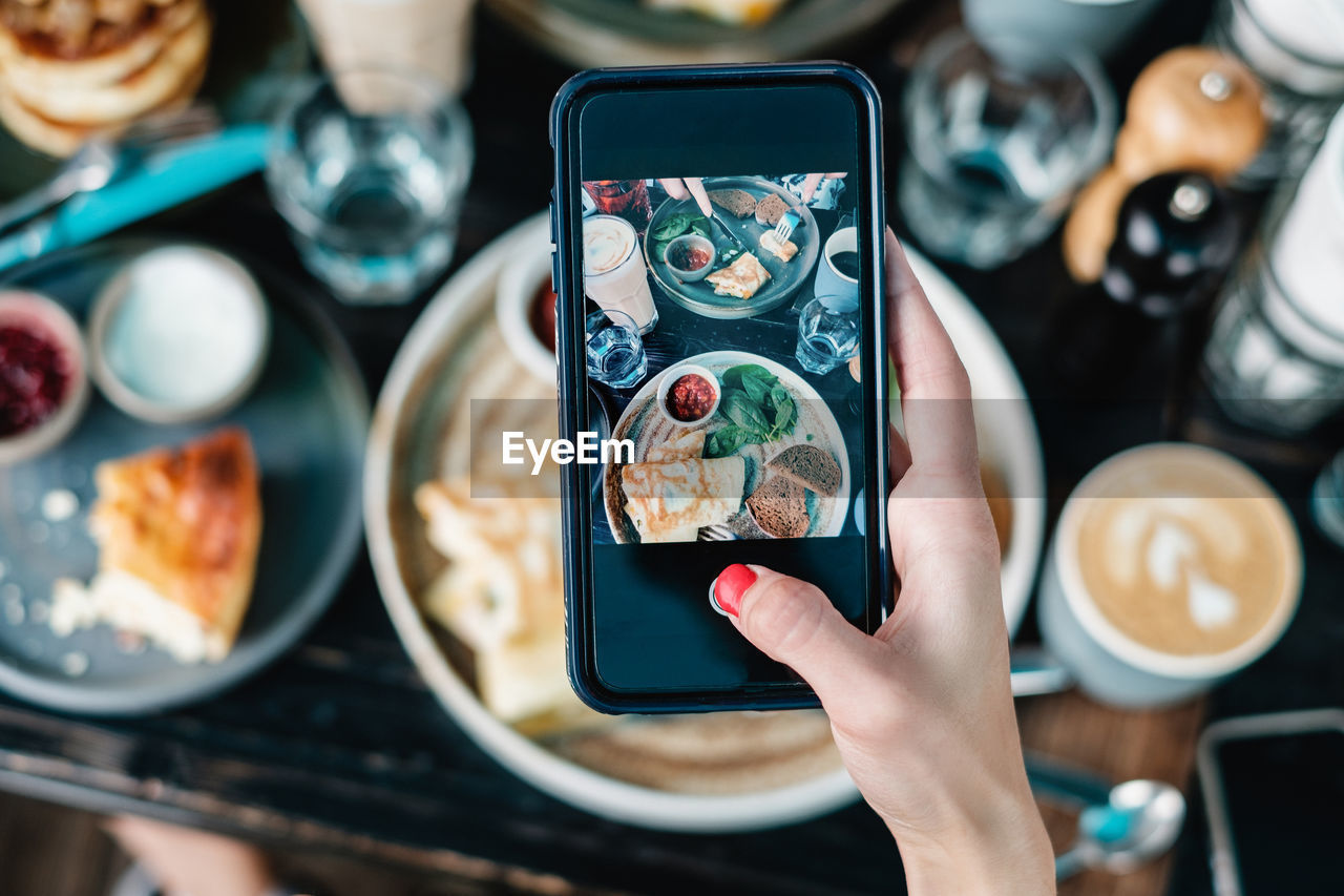 Cropped Hand Of Woman Photographing Food Served On Table