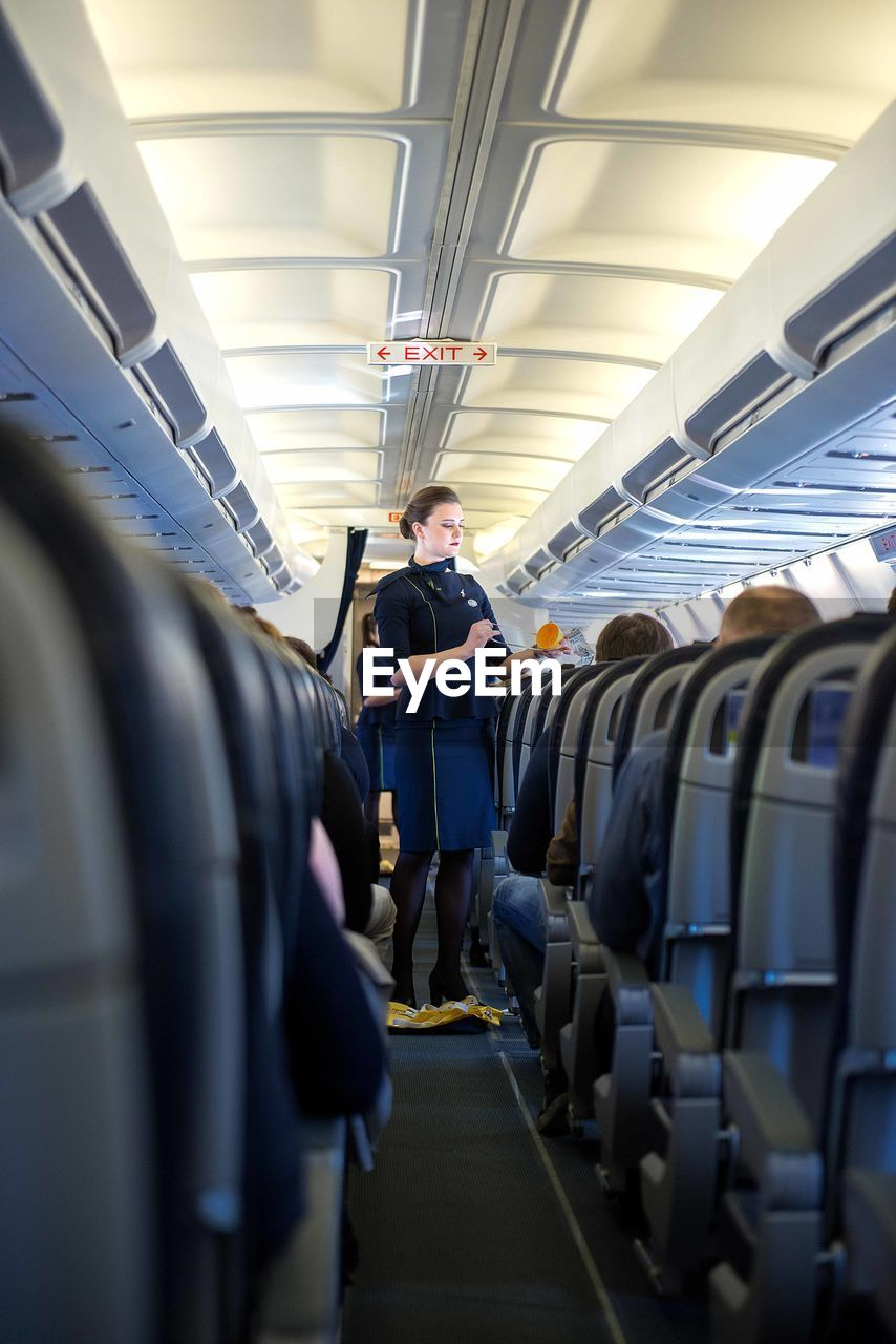 travel, transportation, airplane, mode of transportation, vehicle interior, public transportation, real people, air vehicle, one person, vehicle seat, journey, seat, passenger, men, indoors, lifestyles, rail transportation, standing, in a row, airplane seat, uniform