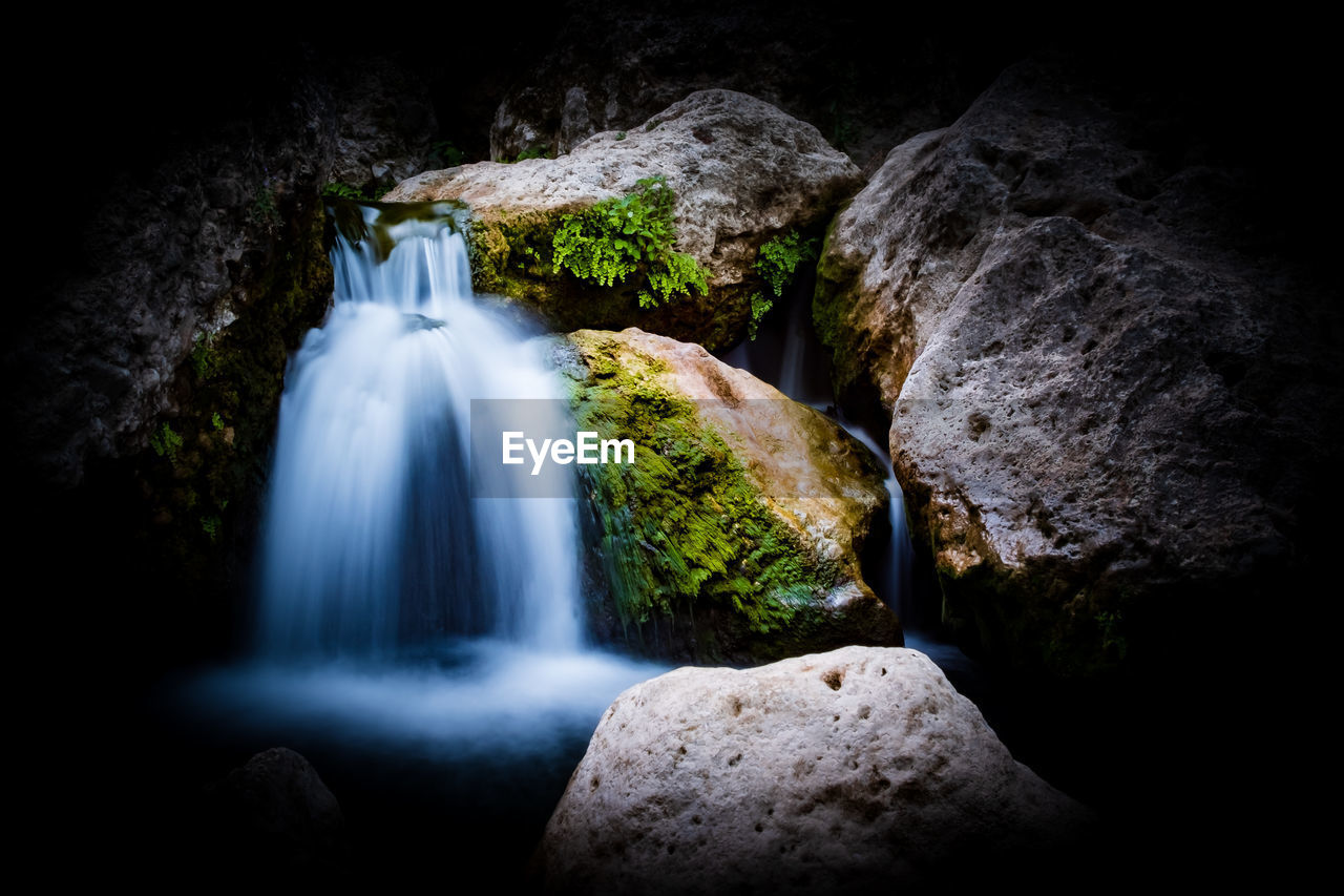 long exposure, solid, rock, rock - object, motion, waterfall, no people, scenics - nature, beauty in nature, blurred motion, water, rock formation, flowing water, nature, land, moss, forest, outdoors, plant, flowing, black background