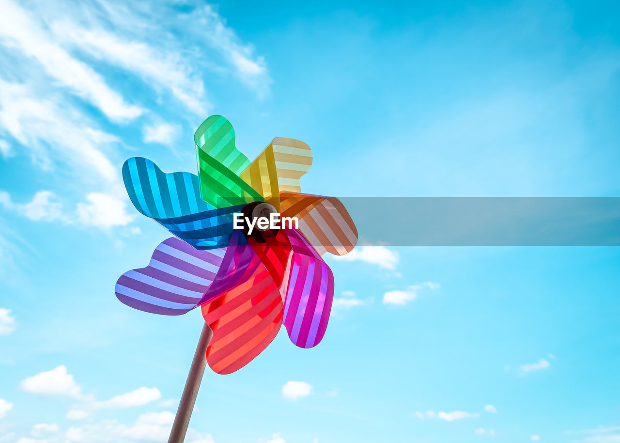 Low angle view of multi colored wind turbine against blue sky