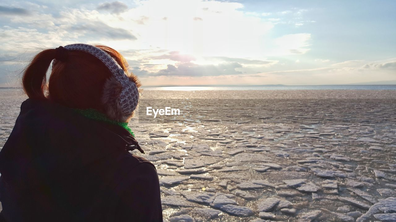Close-up of woman wearing headphones at beach against sky during winter