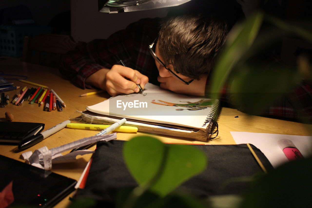real people, child, one person, indoors, art and craft, concentration, childhood, lifestyles, selective focus, creativity, men, table, paper, males, drawing - activity, boys, leisure activity, publication, book, studying