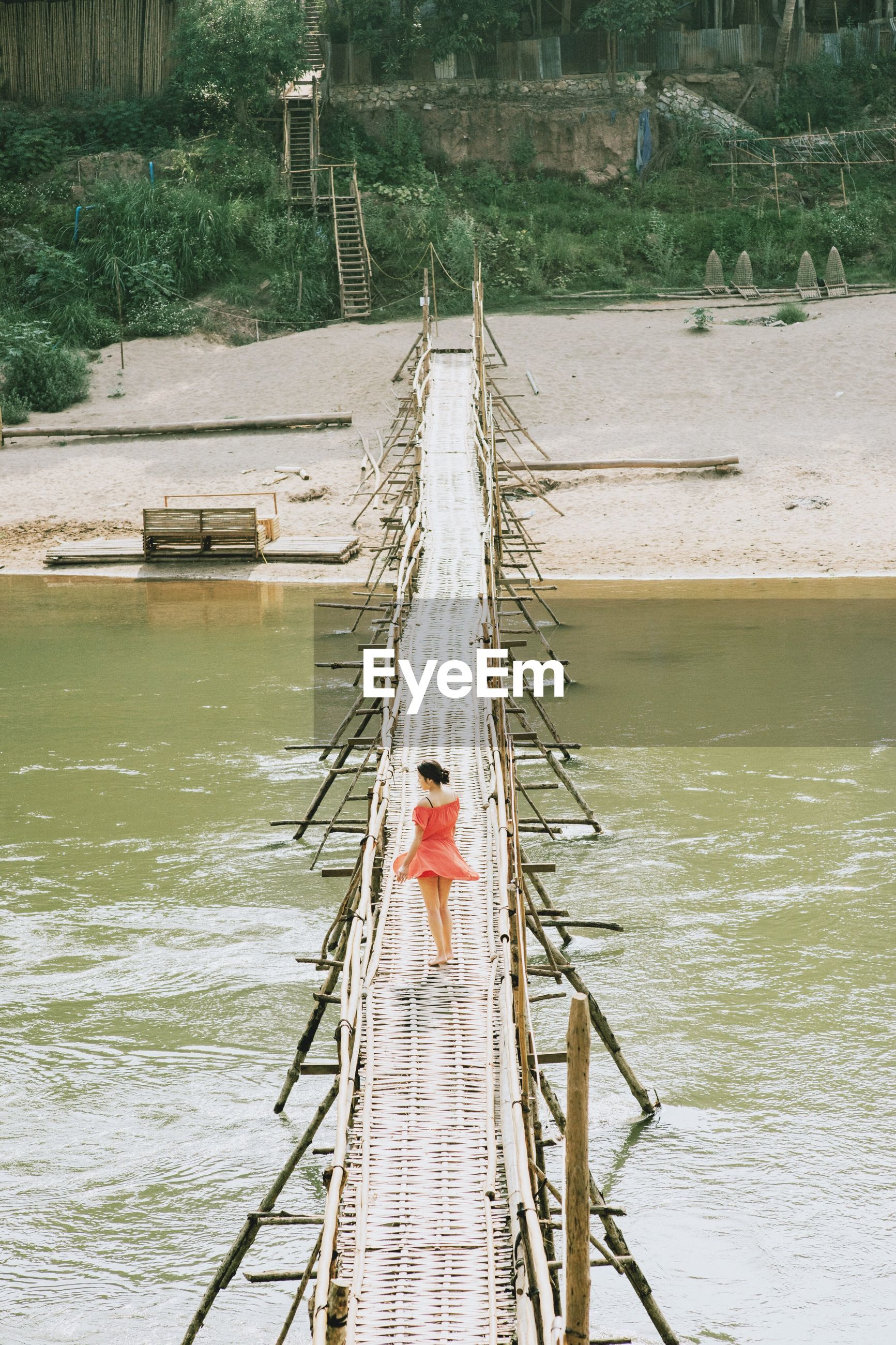 Woman walking on bridge over sea