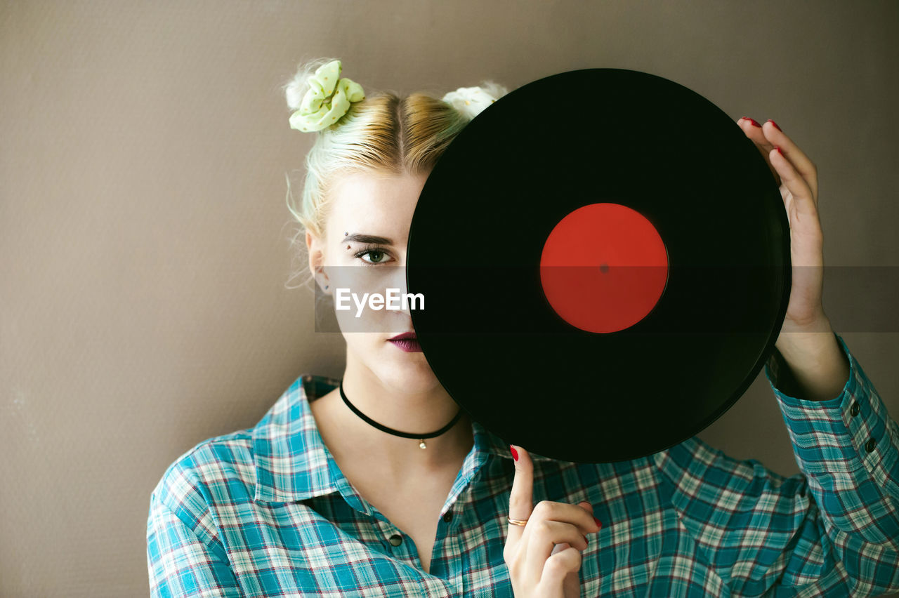 Portrait of young woman holding record against beige background