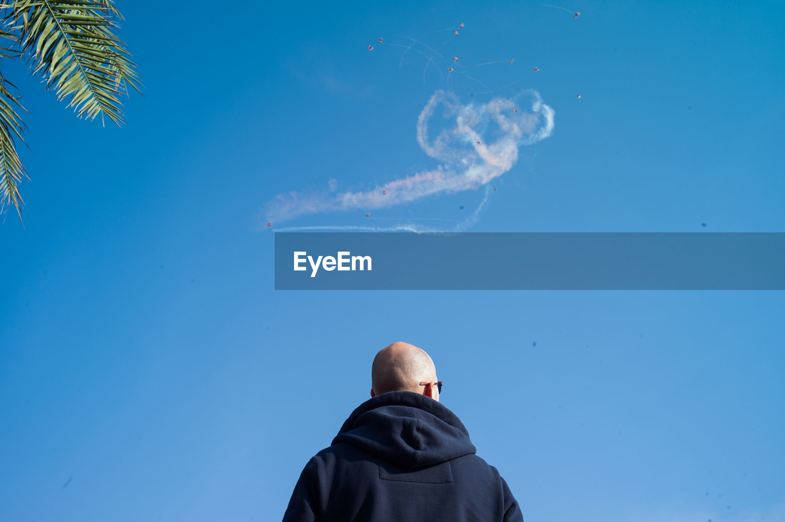 Low angle view of man against vapor trail in sky on sunny day