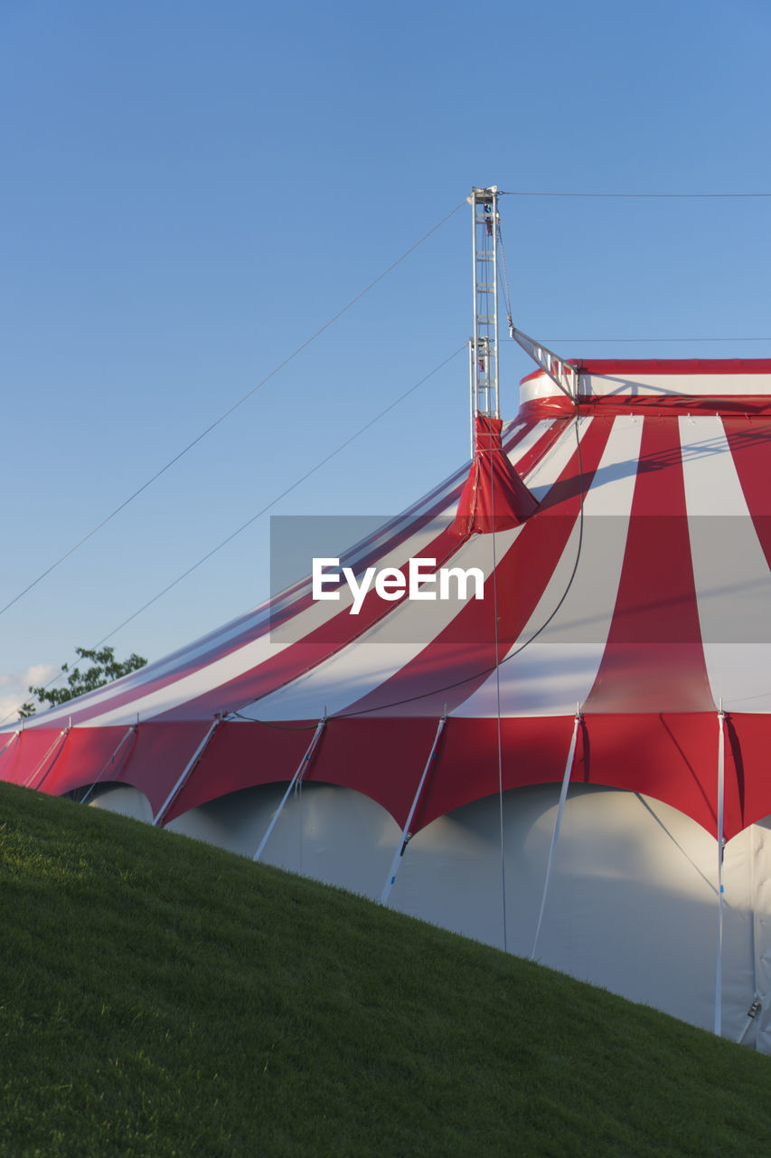Low Angle View Of Circus Tent On Field Against Clear Blue Sky
