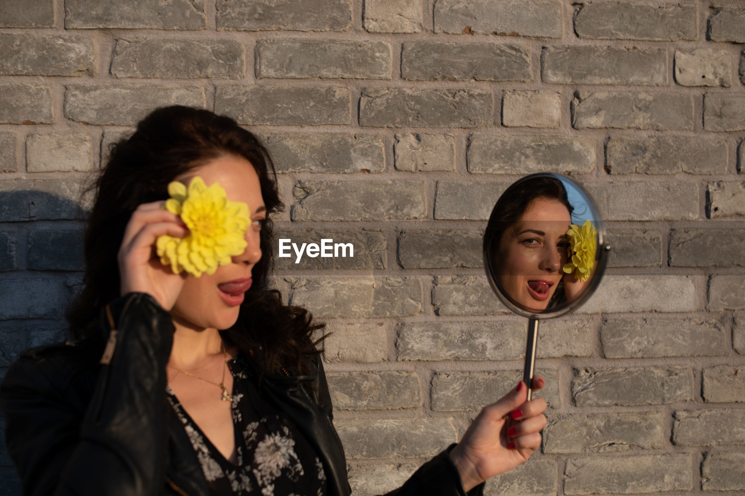 Woman holding yellow flower and mirror with reflection against brick wall