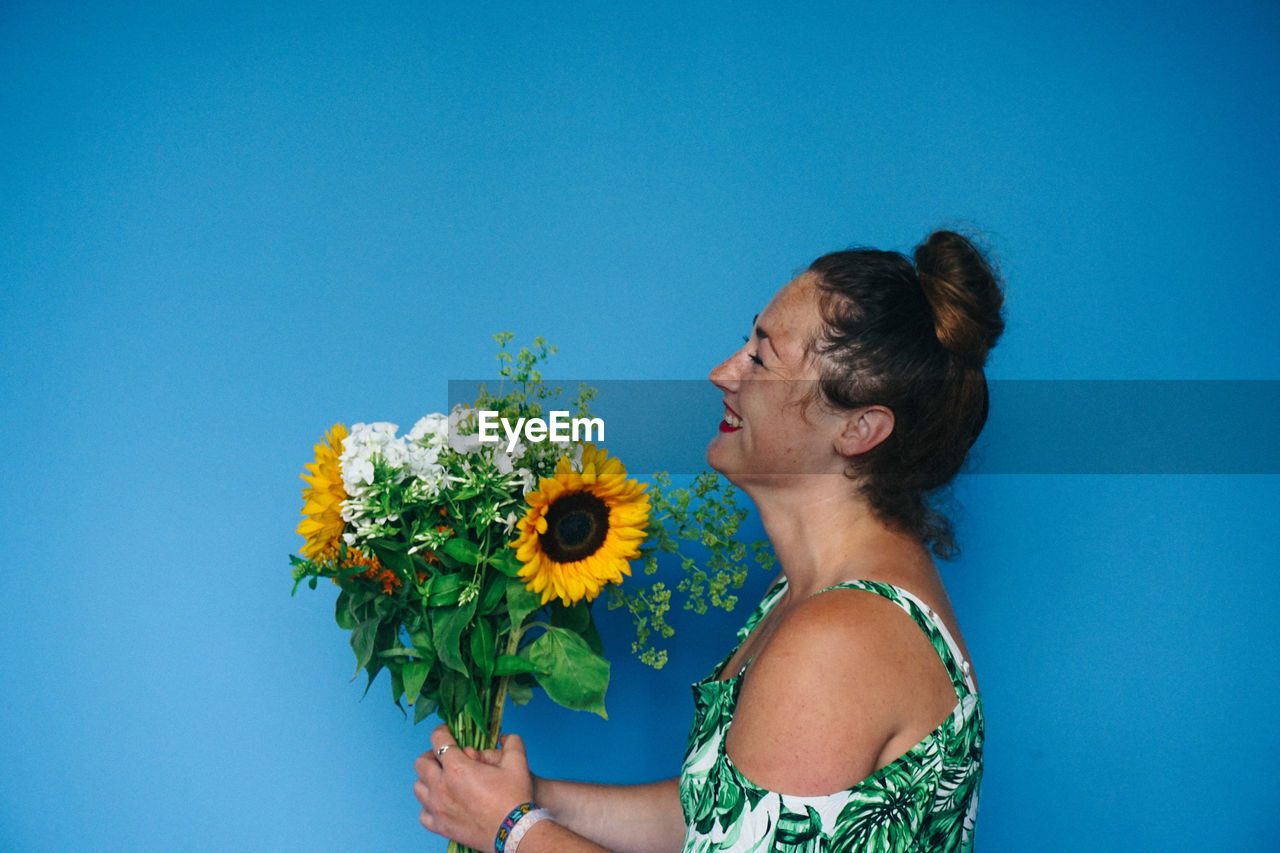 Woman Holding Flowers Against Blue Background