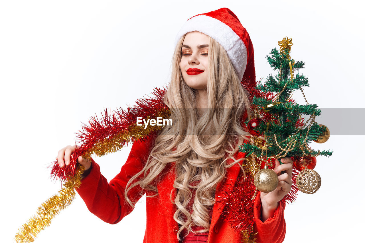 PORTRAIT OF BEAUTIFUL YOUNG WOMAN WITH CHRISTMAS TREE