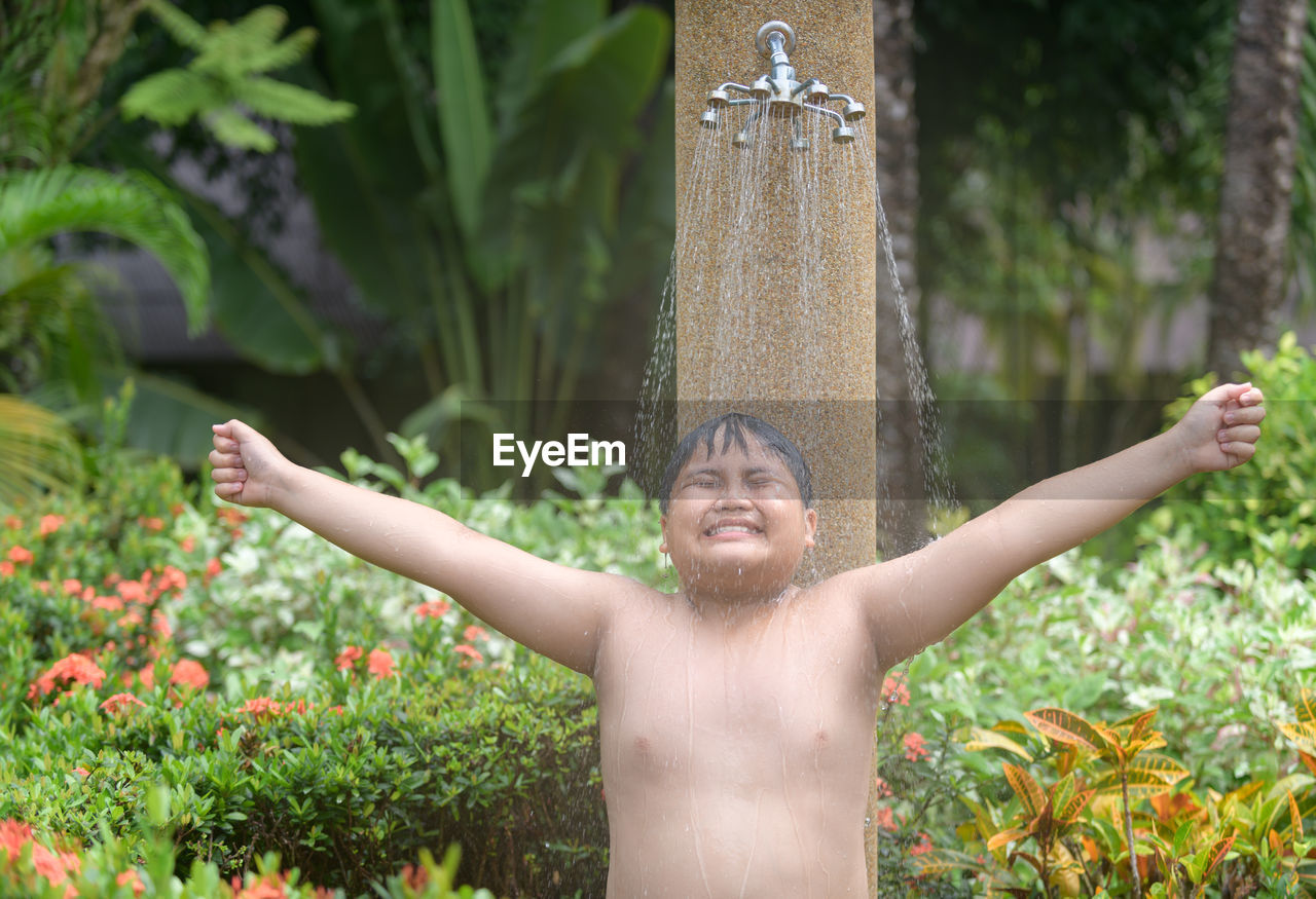 plant, real people, one person, human arm, lifestyles, leisure activity, growth, nature, day, front view, smiling, happiness, standing, tree, shirtless, limb, child, emotion, waist up, portrait, arms raised, outdoors