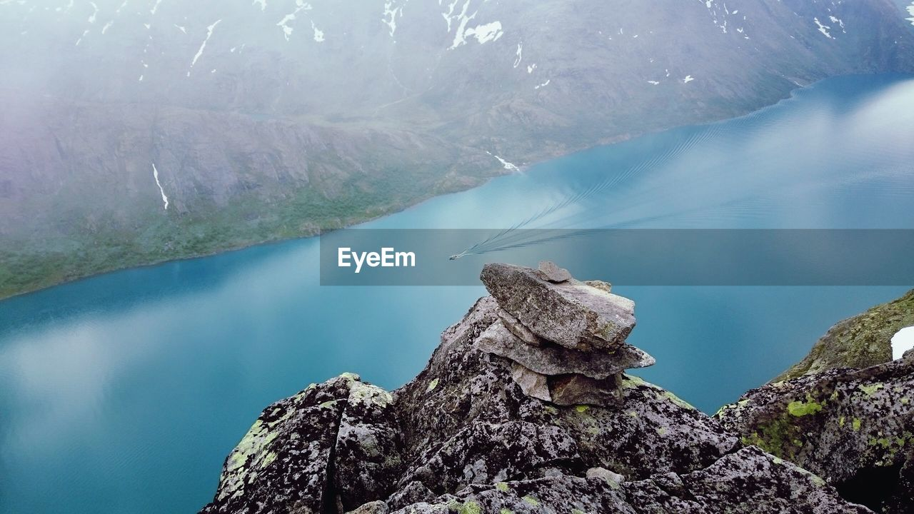 High Angle View Of Rock By Lake Against Mountain