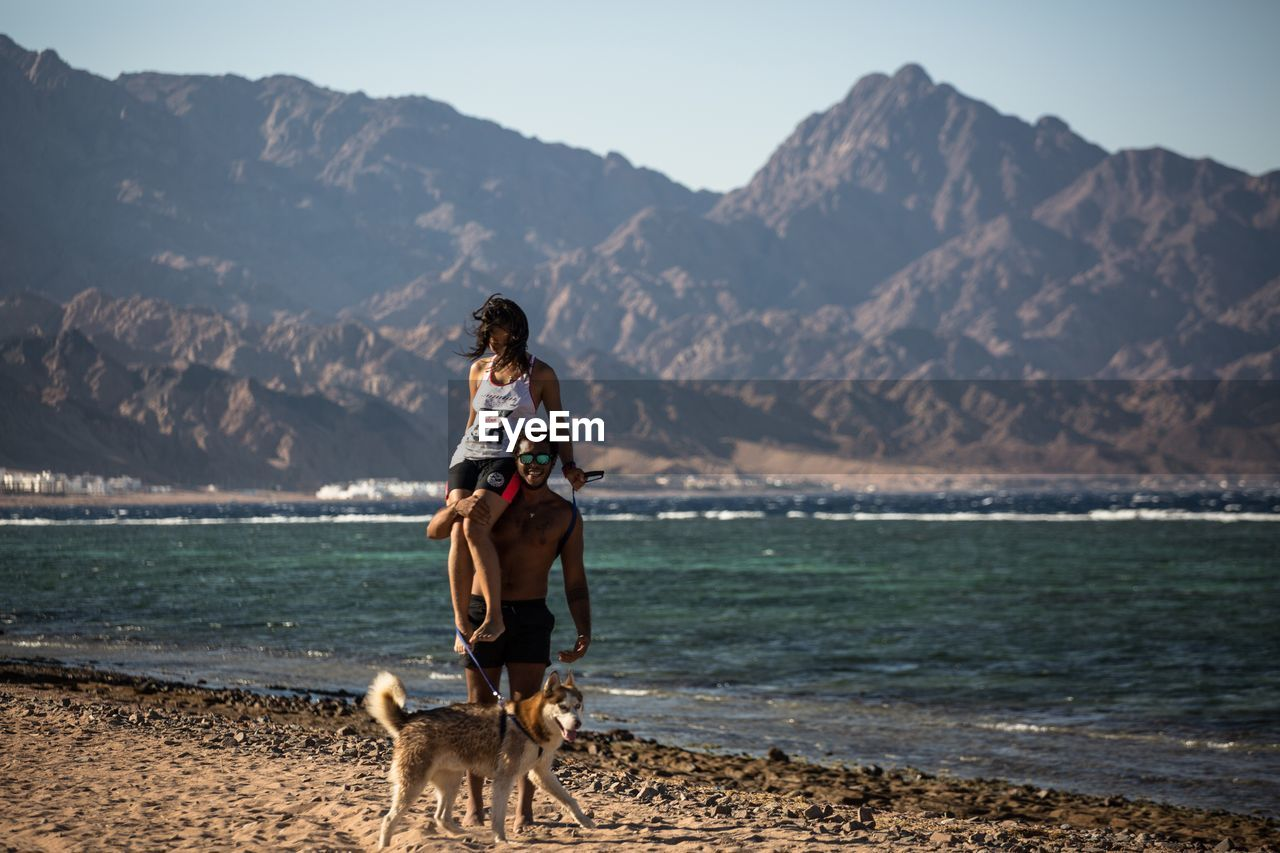 WOMAN WITH DOG AT BEACH AGAINST MOUNTAINS