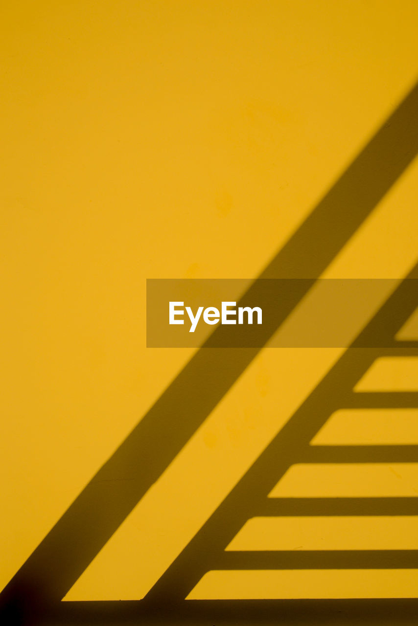 shadow, yellow, wall - building feature, full frame, sunlight, backgrounds, no people, pattern, copy space, built structure, architecture, indoors, close-up, nature, day, orange color, focus on shadow, colored background, abstract