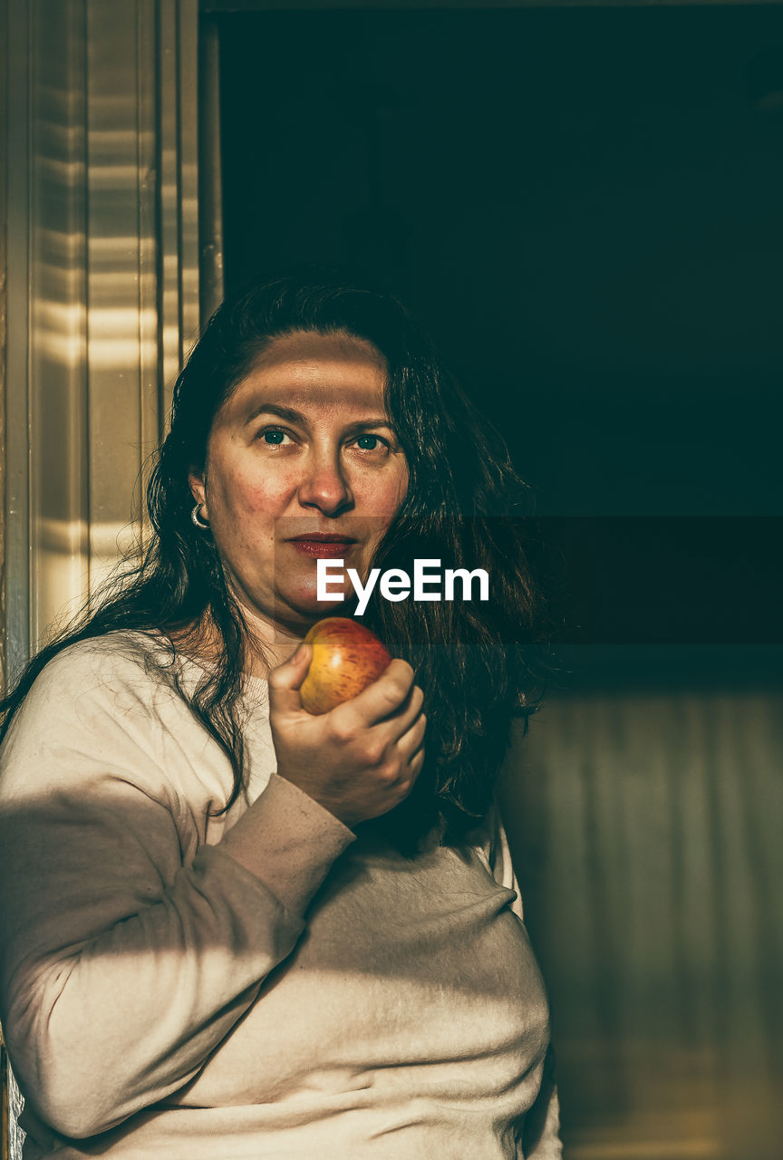 Portrait of woman holding apple