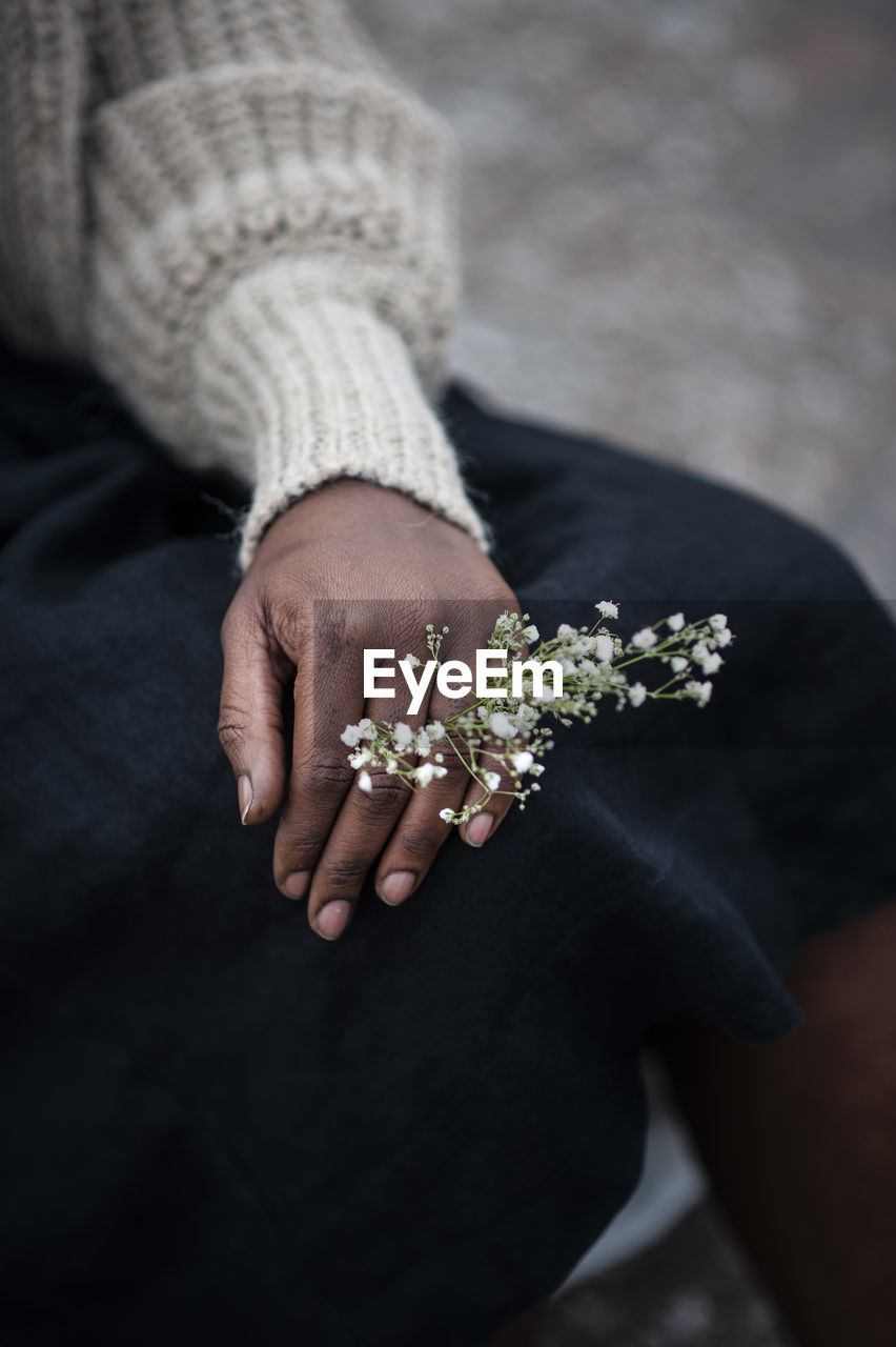 human hand, real people, hand, human body part, one person, women, midsection, lifestyles, adult, holding, flower, flowering plant, focus on foreground, jewelry, high angle view, leisure activity, day, sitting, close-up, finger, human limb