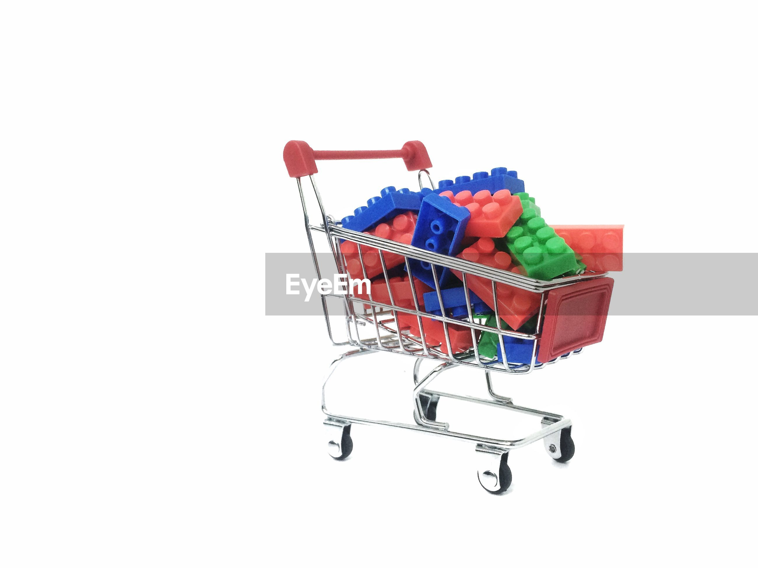 Close-up of toy blocks in shopping cart against white background