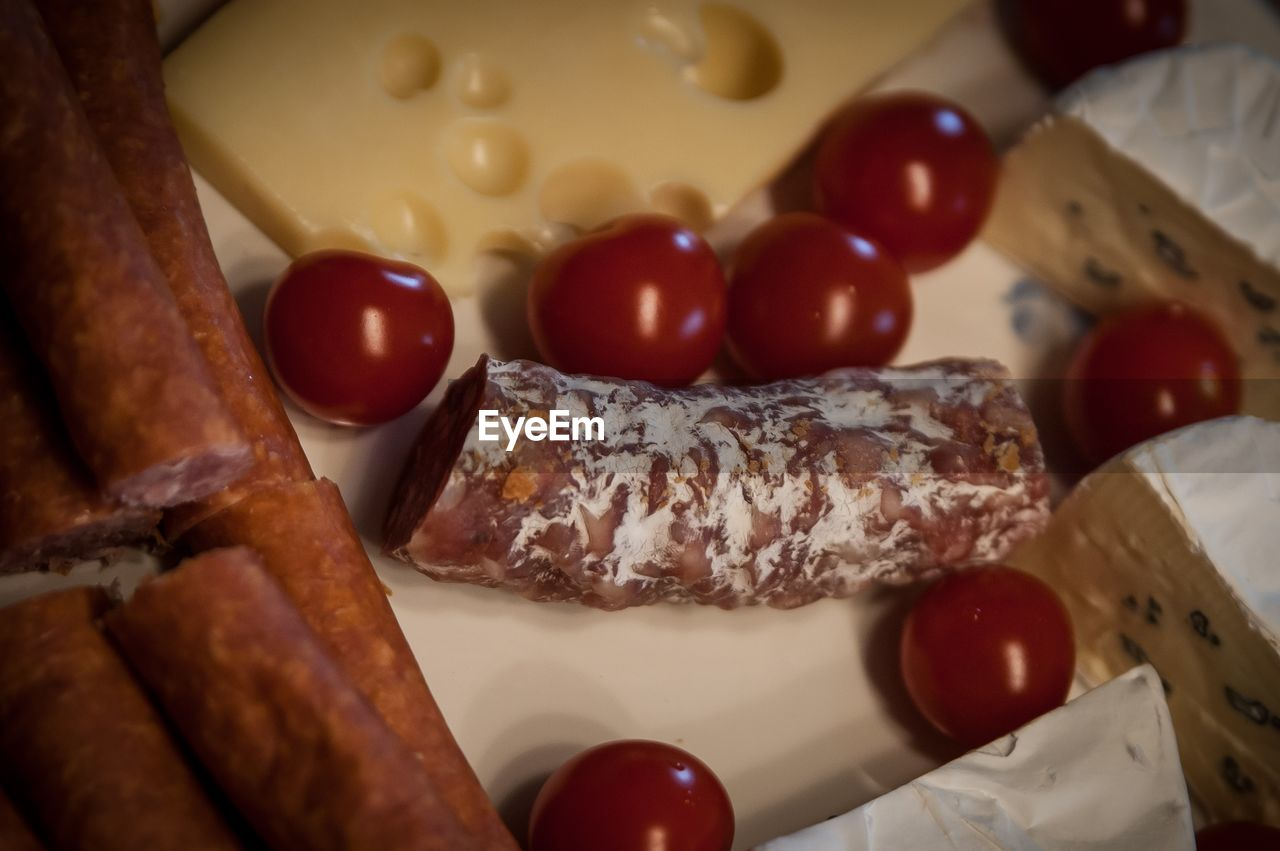 Close-Up Of Sausages With Cherry Tomatoes And Cheese