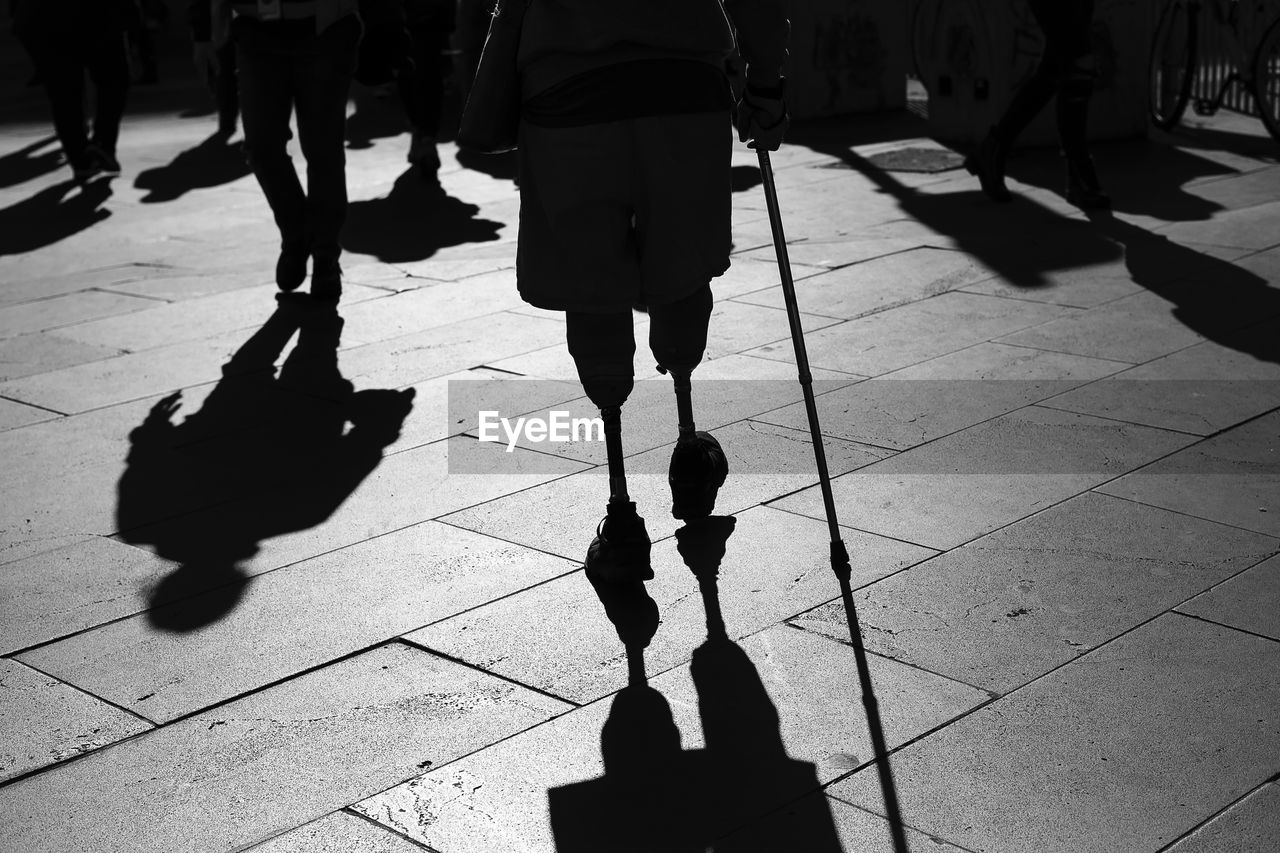 Low Section Of Person With Prosthetic Legs Walking On Footpath In City