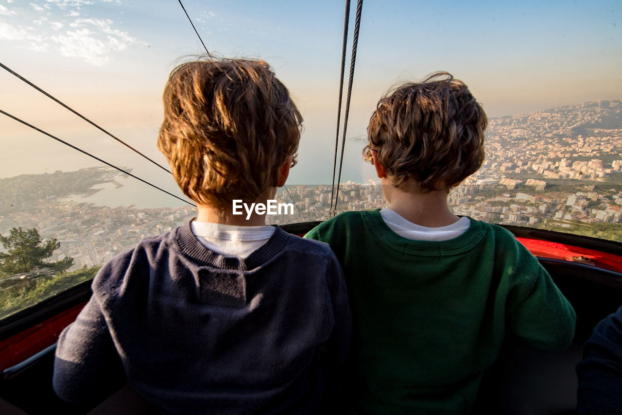 Rear View Of Boys In Overhead Cable Car