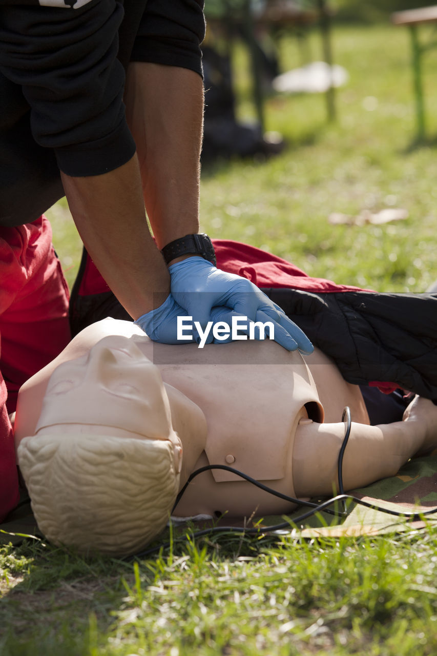 Midsection of woman learning cpr on grassy field