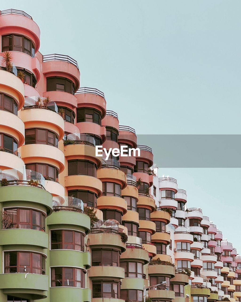 low angle view, built structure, architecture, sky, building exterior, clear sky, day, building, no people, nature, copy space, city, outdoors, in a row, sunlight, residential district, roof, repetition, balcony, order, apartment