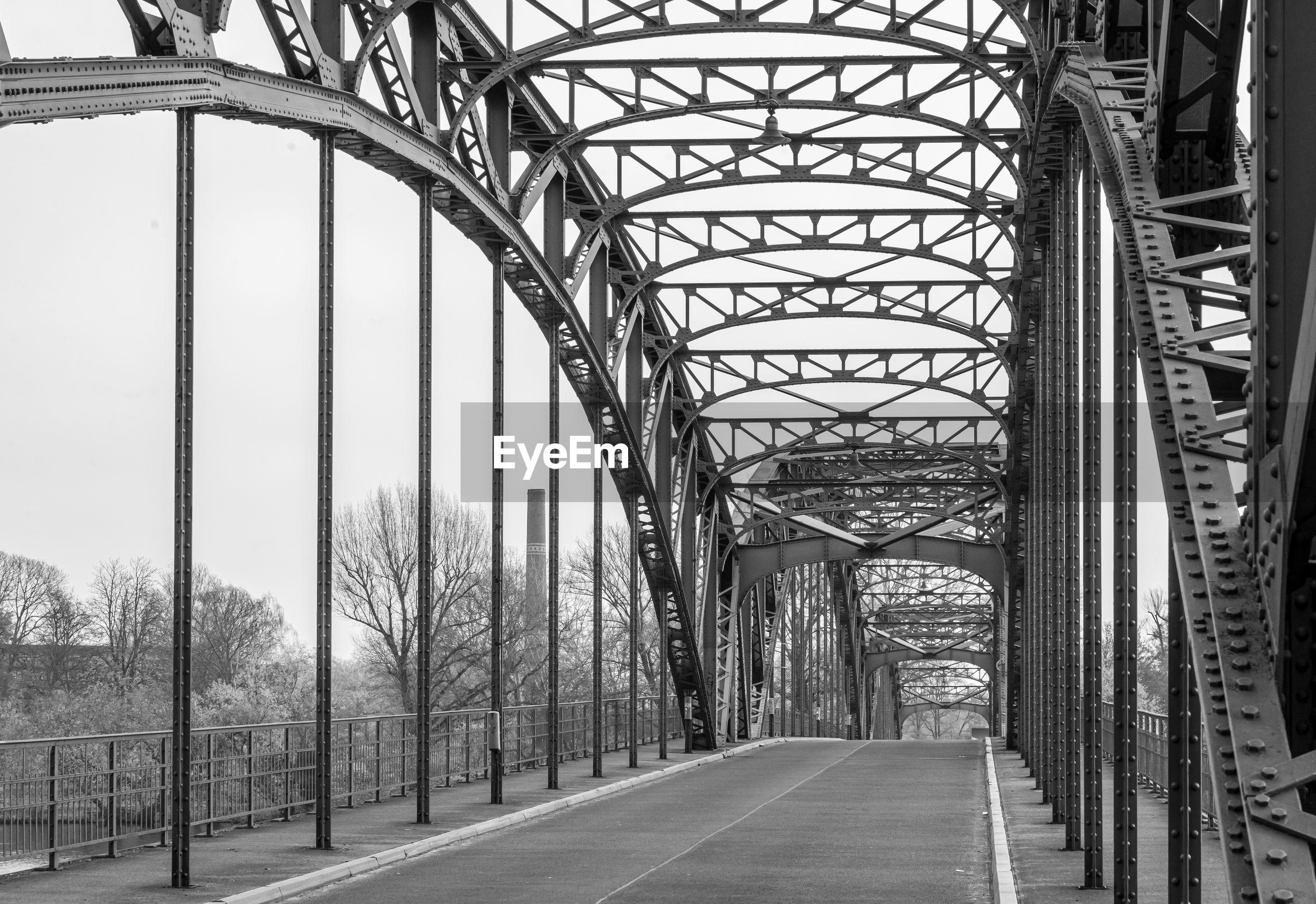 Empty road along bridge in city