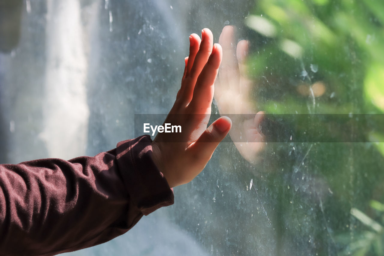 Midsection of person on wet glass during rainy season