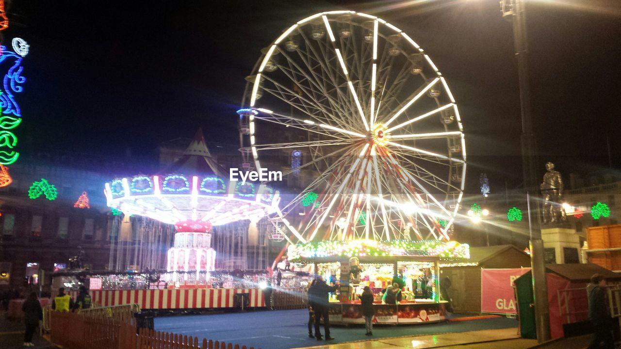 illuminated, amusement park, night, arts culture and entertainment, leisure activity, amusement park ride, group of people, outdoors, women, men, large group of people, real people, carousel, sky, people