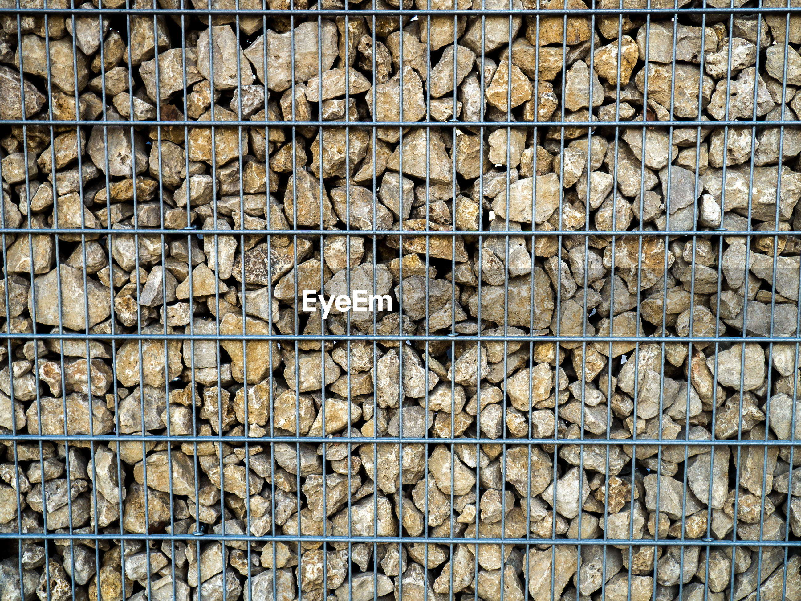 High angle view of metal grate and rocks