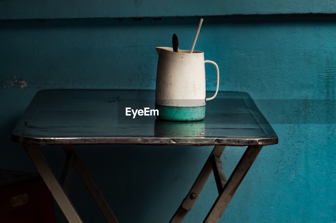 table, no people, wood - material, day, container, indoors, wall - building feature, still life, metal, drink, food and drink, close-up, cup, household equipment, refreshment, old, straw, seat