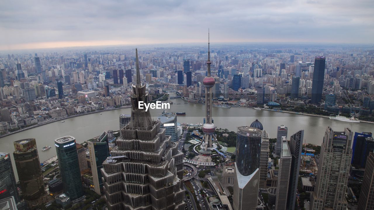city, architecture, skyscraper, cityscape, building exterior, built structure, tower, sky, modern, high angle view, travel destinations, no people, aerial view, cloud - sky, outdoors, urban skyline, water, day