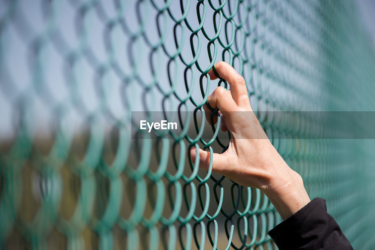Cropped image of hand on chainlink fence