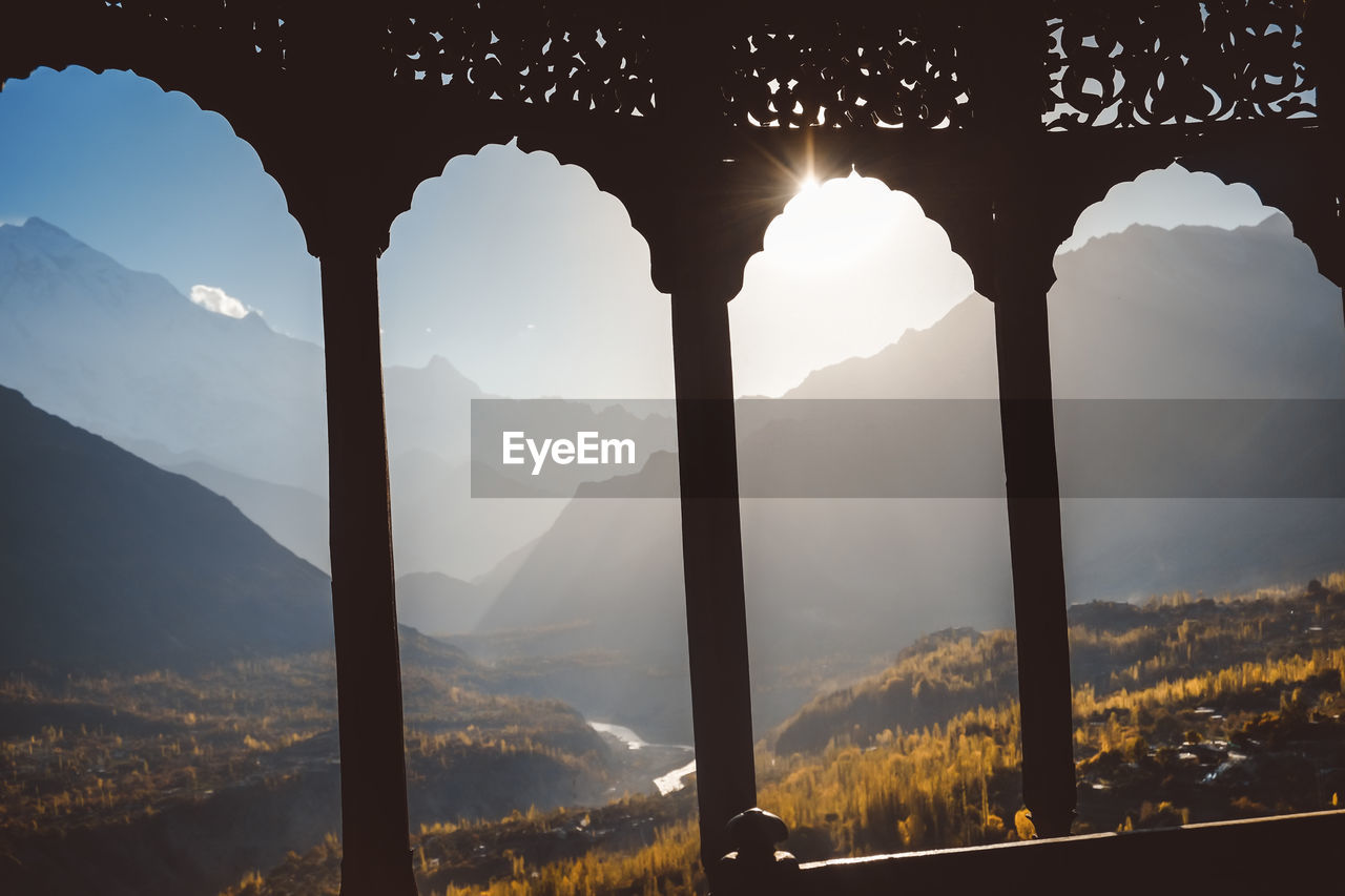 mountain, mountain range, sky, beauty in nature, scenics - nature, nature, architecture, sunlight, tranquil scene, no people, tranquility, built structure, non-urban scene, environment, day, outdoors, sun, cloud - sky, landscape, idyllic, lens flare, mountain peak