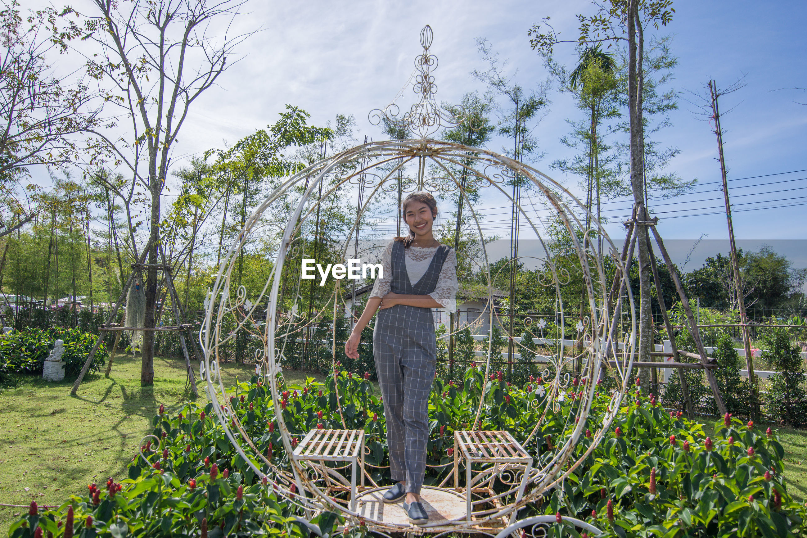 Portrait of woman standing on metallic structure by plants against sky