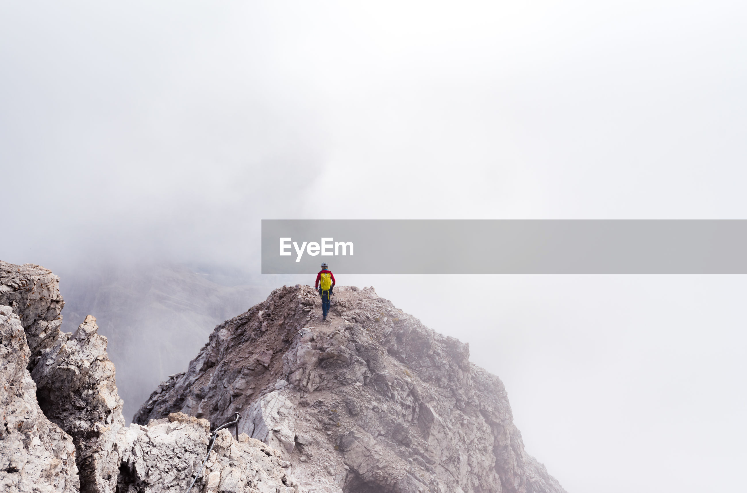 Rear view of person on rock in mountains against sky