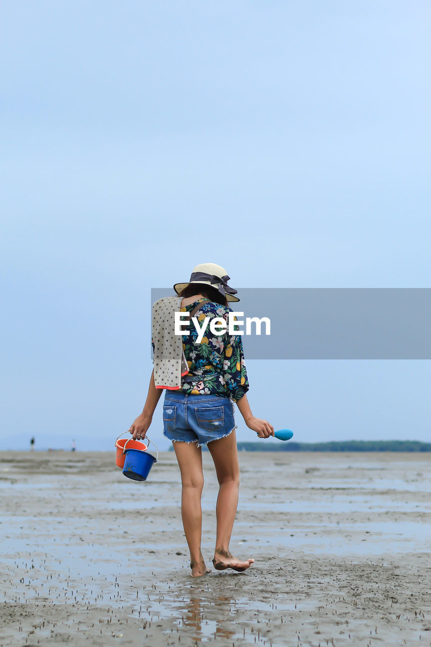 beach, full length, land, real people, leisure activity, one person, lifestyles, sea, sky, rear view, water, vacations, trip, hat, clothing, walking, scenics - nature, holiday, nature, women, outdoors, shorts