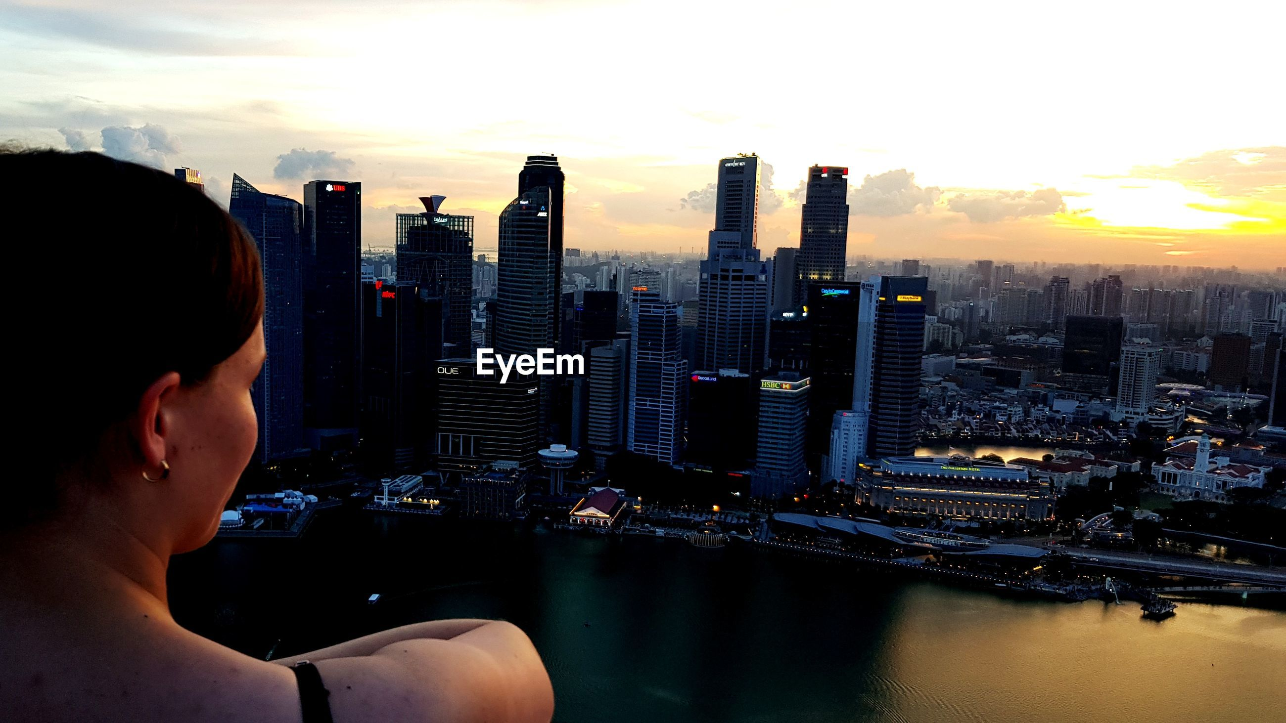 Man looking at cityscape against sky during sunset