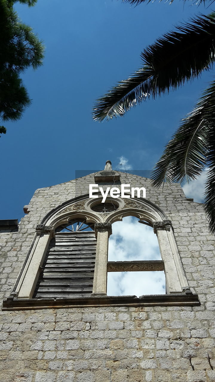 low angle view, architecture, built structure, tree, day, building exterior, palm tree, outdoors, no people, place of worship, sky, bell, spirituality, religion, travel destinations, bell tower